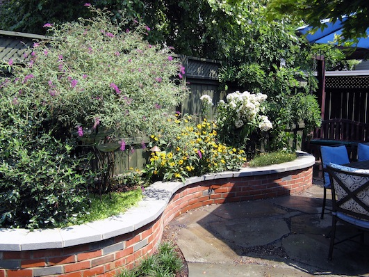 Row House Backyard Ideas : Garden blooming behind the undulating brick seat wall with bluestone